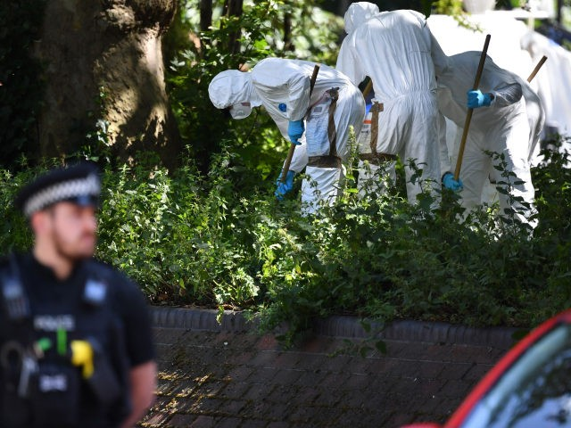 Police forensics officers dressed in Tyvek protective PPE (personal protective equipment) suits and wearing masks, conduct a search as they work outside the walls of Forbury Gardens park in Reading, west of London, on June 22, 2020, the scene of the June 20 stabbing spree. - A suspect held on …