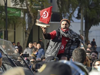 A Tunisian protester lifts a flag-clad birdcage during an anti-government demonstration on the Habib Bourguiba avenue in the capital Tunis, on January 19, 2021. - Tunisia braced for further protests after hundreds were arrested in four nights of street clashes between riot police and disaffected youths in cities across the …
