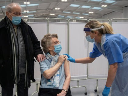 MANSFIELD, ENGLAND - JANUARY 25: Geoff Holland, 90, and Jenny Holland, 86, from Mansfield receive their injections of the AstraZeneca coronavirus vaccine at a former Wickes store in Mansfield, Nottinghamshire, which is being used as a covid vaccination centre on January 25, 2021 in Mansfield, England. The couple, who met …