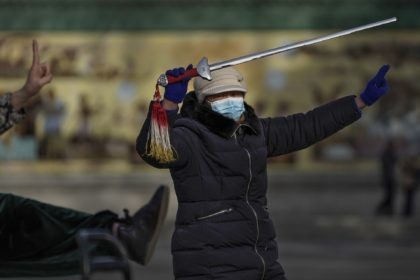 A woman wearing a face mask to help curb the spread of the coronavirus performs a morning exercise with a sword at a public park in Beijing, Tuesday, Jan. 12, 2021. Lockdowns have been expanded and a major political conference postponed in a province next to Beijing that is the …
