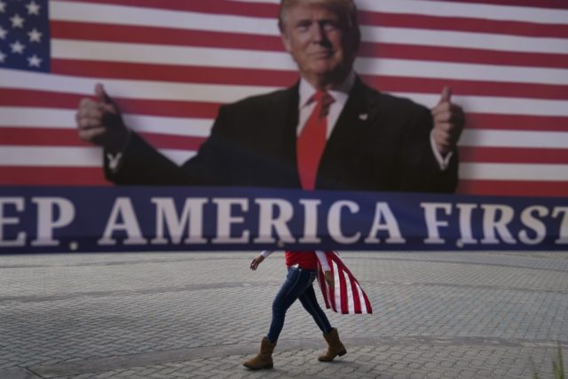 In this Jan. 6, 2021, file photo, a woman draped in an American flag walks past a banner supporting President Donald Trump during a rally in Huntington Beach, Calif. For America's allies and rivals alike, the chaos unfolding during Donald Trump's final days as president is the logical result of …