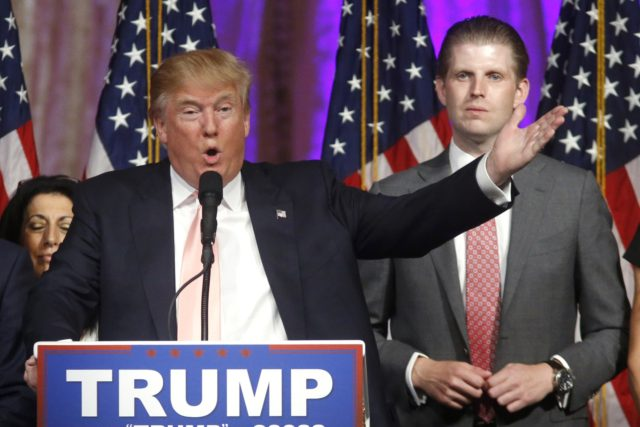 In this Tuesday, March 15, 2016, file photo, Republican presidential candidate Donald Trump speaks to supporters at his primary election night event at his Mar-a-Lago Club in Palm Beach, Fla. At right is his son Eric Trump. Hits to President Donald Trump's business empire since the deadly riots at the …