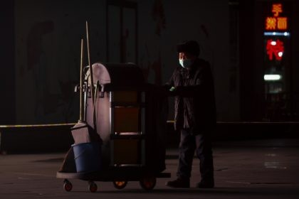 A maintenance worker wearing a face mask to protect against the spread of the coronavirus walks outside of an office complex in Beijing, Wednesday, Jan. 13, 2021. China is concentrating its pandemic prevention efforts in the rural areas as officials urge people to not travel home for the annual Lunar …