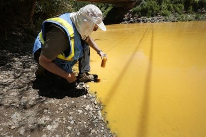 In this Aug. 6, 2015, file photo, Dan Bender of the La Plata County Sheriff's Office takes a water sample from the Animas River near Durango, Colo., after the accidental release of an estimated 3 million gallons of waste from the Gold King Mine. The Navajo Nation's Department of Justice …
