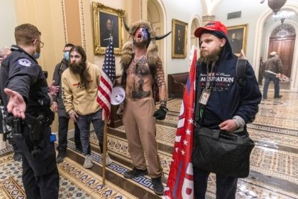 In this Wednesday, Jan. 6, 2021 file photo, supporters of President Donald Trump, including Jacob Chansley, center with fur hat, are confronted by Capitol Police officers outside the Senate Chamber inside the Capitol in Washington. Chansley's lawyer says that he reached out White House Chief of Staff Mark Meadows about …