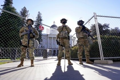 California National Guard members stand guard at an access point to the California state Capitol in Sacramento, Calif., Tuesday, Jan. 19, 2021. A temporary 6-foot high chain link fence surrounds the Capitol and California Gov. Gavin Newsom mobilized the National Guard last week over concerns that protests around Wednesday's inauguration …