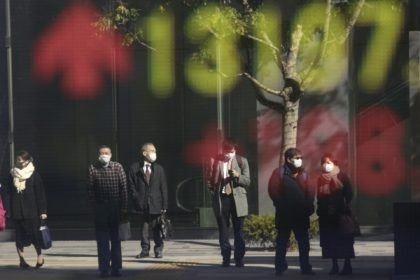 People are reflected on the electronic board of a securities firm in Tokyo, Wednesday, Jan. 20, 2021. Asian shares were mostly higher Wednesday, ahead of Joe Biden's inauguration as president, ending President Donald Trump's four-year term. Japan's benchmark lost early gains as worries grew about the surge in coronavirus cases. …