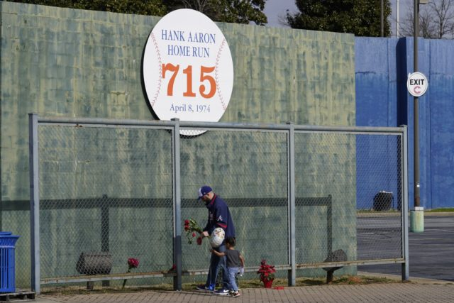 Les Motes and his two-year-old daughter Mahalia leave flowers, Friday, Jan. 22, 2021, in Atlanta, near the spot where a ball hit for a home run by Atlanta Braves' Hank Aaron cleared the wall to break Babe Ruth's career home run record in 1974. Aaron, who endured racist threats with …
