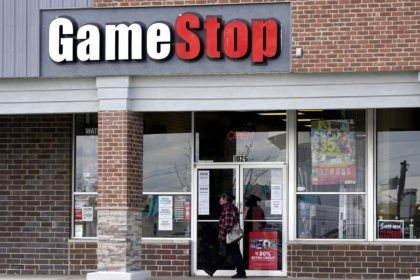 A woman wears a face mask as she walks past a GameStop store in Des Plaines, Ill., Thursday, Oct. 15, 2020. The latest battleground between the proletariat and the hedge funds serving the 1% isn't on just any street. It's on Wall Street. At least, that's the view within an …