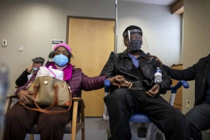 In this Jan. 23, 2021, file photo, Dorothy Kade, left, holds the hand of her husband, Walter Kade Jr., as they wait in the observation room after he received a COVID-19 vaccine at the VA Medical Center, in Philadelphia. (Tyger Williams/The Philadelphia Inquirer via AP, File)