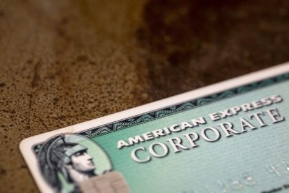 This Aug. 11, 2019 file photo shows an American Express card in New Orleans. American Express Co. says its fourth-quarter net income fell 15% to $1.44 billion as the coronavirus pandemic continued to impact its bottom line. On a per-share basis, the New York-based company said Tuesday, Jan. 26, 2021, …