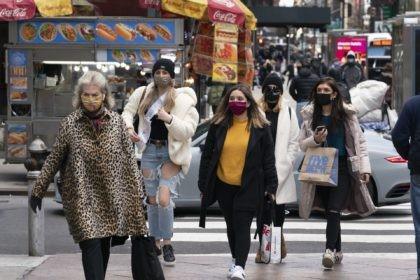 Women carry shopping bags, Thursday, Dec. 10, 2020, in New York. The spread of COVID-19 vaccines will power a stronger global economic recovery in 2021, the International Monetary Fund forecast Tuesday, Jan. 26, 2021. (AP Photo/Mark Lennihan)