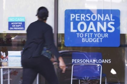 In this Oct. 1, 2020 file photo, a woman walks past a personal finance loan office in Franklin, Tenn. According to information released Tuesday, Jan. 26, 2021, credit reporting agency TransUnion has found that nearly 3% of common consumer debts were in financial-hardship status at the end of 2020, illustrating …