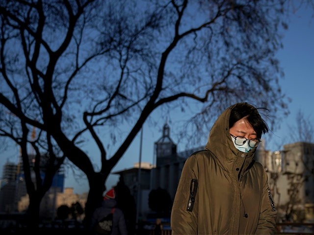 A woman wearing a face mask to help curb the spread of the coronavirus walks on a street as the capital city is hit by cold wind in Beijing, Wednesday, Jan. 6, 2021. (AP Photo/Andy Wong)