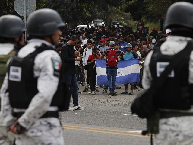 Mexican National Guards stand by as Central American migrants, who crossed the nearby border from Guatemala, stand on a highway leading to Tapachula, Mexico, Thursday, Jan. 23, 2020. Hundreds of Central American migrants crossed the Suchiate river into Mexico from Guatemala Thursday after a days-long standoff with security forces. (AP …