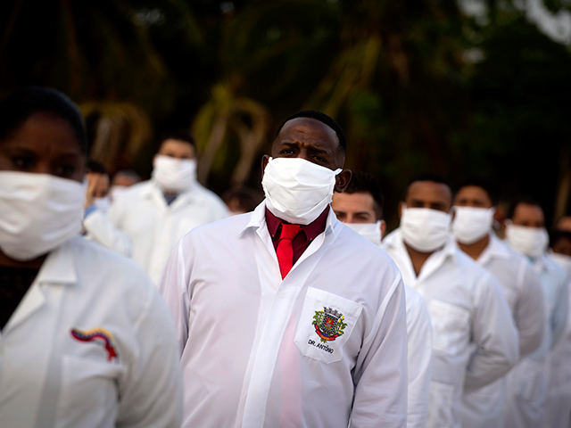A brigade of health professionals, who volunteered to travel to South Africa to assist local authorities with an upsurge of coronavirus cases, attend the farewell ceremony in Havana, Cuba, Saturday, April 25, 2020. (AP Photo/Ramon Espinosa)