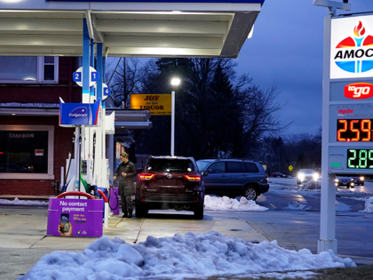 A customer checks gas price and ready to fill up a gas tank at the Amoco gas station in Glenview, Ill., Saturday, Jan. 16, 2021. Gas prices have gone up about 20 cents over the past month according to Gas Buddy analysts. (AP Photo/Nam Y. Huh)