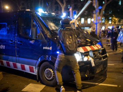 A demonstrator hits a police van with a bat during clashes following a protest condemning the arrest of rap singer Pablo Hasél in Barcelona, Spain, Wednesday, Feb. 17, 2021. Police fired rubber bullets and baton-charged protesters as clashes erupted for a second night in a row Wednesday at demonstrations over …