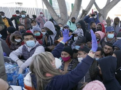 A woman handing out food and water speaks to asylum seekers waiting in Mexico, Friday, Feb. 19, 2021, in Tijuana, Mexico. After waiting months and sometimes years in Mexico, people seeking asylum in the United States are being allowed into the country starting Friday as they wait for courts to …