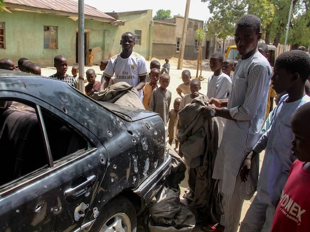 The wreckage of a car hit by an attack led by Boko Haram members is seen surrounded by residents of the Adam Kolo district of Maiduguri on February 24, 2021. - Boko Haram jihadists attacked the Nigerian city of Maiduguri in the volatile northeast, killing 10 to 17 people, including …