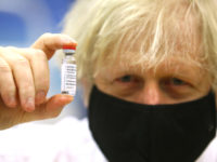 CWMBRAN, WALES – FEBRUARY 17: British Prime Minister Boris Johnson poses with a vial of the Oxford/AstraZeneca vaccine during a visit to the vaccination centre at Cwmbran Stadium on February 17, 2021 in Cwmbran, Wales. The Prime Minister visited the vaccination centre to see the progress of the COVID-19 vaccine …