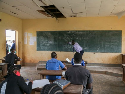 A teacher wearing a face shield as a preventive measure against the spread of the COVID-19 coronaviruswrites on the board at the Technical High School of Nkol-Bisson in Yaoundé, Cameroon, on June 1, 2020. - Cameroon's schools and universities reopened on Monday as the government was criticised over weak measures …