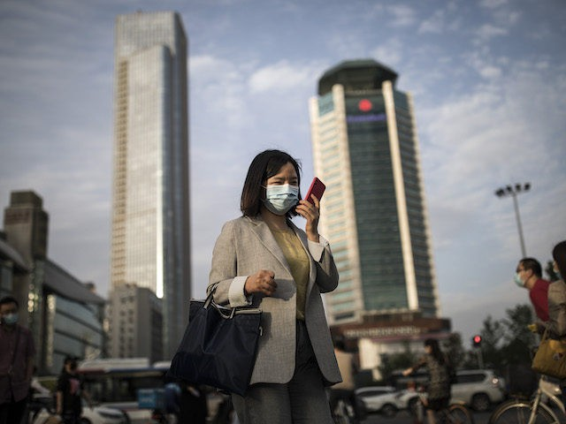 A women wears a mask while uses iPhone pass the crossroads on May 11, 2020 in Wuhan, China. (Getty Images)