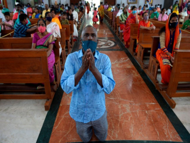 Christian devotees wearing facemasks as a preventive measure against the Covid-19 coronavirus offer prayers at Sacred Heart Shrine Church on Christmas in Chennai on December 25, 2020. (Photo by Arun SANKAR / AFP) (Photo by ARUN SANKAR/AFP via Getty Images)