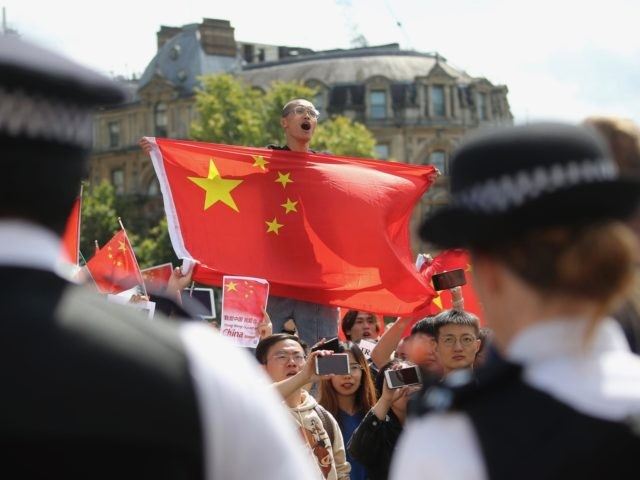 Counter-protesters hold up Chinese flags to oppose the protesters gathering in central London to attend a march organised by StandwithHK and D4HK in support of Pro-democracy protests in Hong Kong, on August 17, 2019. - Hong Kong's pro-democracy movement faces a major test this weekend as it tries to muster …