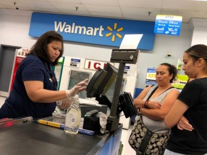 RICHMOND, CALIFORNIA - AUGUST 15: Customers look on as a Walmart cashier rings up their purchases at a Walmart store on August 15, 2019 in Richmond, California. Walmart beat analyst expectations with second quarter revenue of $130.4 billion. Shares of Walmart stock surged 5% in early trading on Thursday. (Photo …