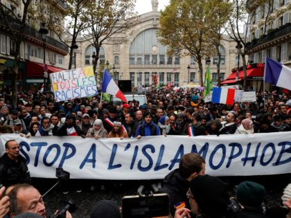 "People wave French national flags, chant slogans and hold placards reading messages such as ""Stop to all types of racism"" (rear L) and ""Stop to Islamophobia"" (front C) as they take part in a demonstration march in front of the Gare du Nord, in Paris to protest against Islamophobia, on …"