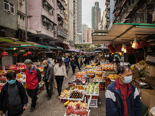 People wearing protective face masks shop at a fresh food market in Hong Kong on February 9, 2020, as a preventative measure after a coronavirus outbreak which began in the Chinese city of Wuhan. - The previously unknown virus has caused alarm because of its similarity to SARS (Severe Acute …
