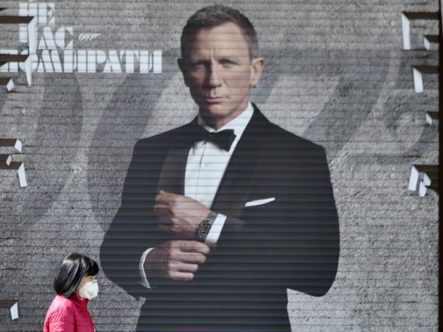 A woman wearing a face mask walks past an image of James Bond actor Daniel Craig in a shop window in the Ukrainian capital of Kiev on April 28, 2020, amid the COVID-19 coronavirus pandemic. (Photo by Sergei SUPINSKY / AFP) (Photo by SERGEI SUPINSKY/AFP via Getty Images)