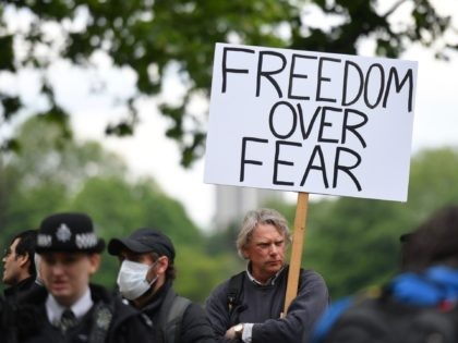 "A man holds a placard that reads ""freedom over fear"" as he attends an anti-coronavirus lockdown demonstration in Hyde Park in London on May 16, 2020, following an easing of lockdown rules in England during the novel coronavirus COVID-19 pandemic. - Fliers advertising 'mass gatherings' organised by the UK Freedom …"