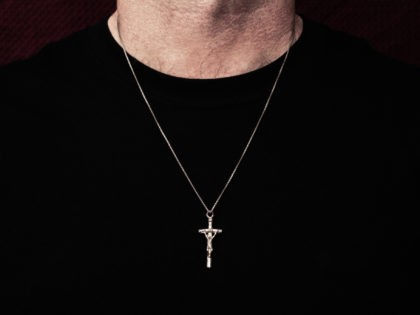 Man wearing silver crucifix pendant