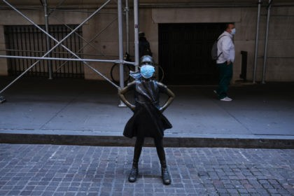 NEW YORK, NY - MAY 07: The Fearless Girl, a bronze statue created by Kristen Visbal and installed for International Women's Day, is shown with a surgical mask affixed across from the New York Stock Exchange (NYSE) on May 07, 2020 in New York City. The Nasdaq turned positive for …