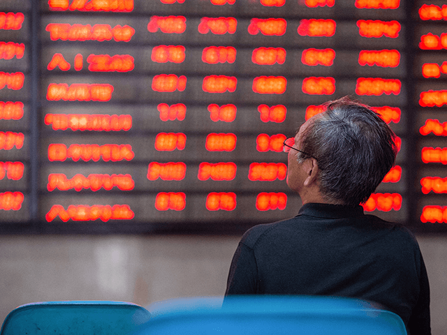 An investor looks at screens showing stock market movements at a securities company in Nanjing in China's eastern Jiangsu province on July 6, 2020. - Shanghai stocks surged on July 6 to a more than two-year high as investors piled in following a combination of rosy predictions for the market …