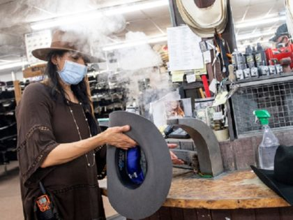 A woman shapes a Stetson hat for a client while wearing a mask at the manufacture store on July 20, 2020, in Garland, Texas, amid the coronavirus pandemic. (Photo by VALERIE MACON / AFP) (Photo by VALERIE MACON/AFP via Getty Images)