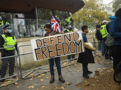 LONDON, ENGLAND - OCTOBER 24: A protester holds a sign reading 'Defend Freedom' during a Unite for Freedom march outside New Scotland Yard on October 24, 2020 in London, England. Hundreds of anti-mask and anti-lockdown protesters marched through central London, England demonstrating against latest Coronavirus lockdown measures. (Photo by Peter …