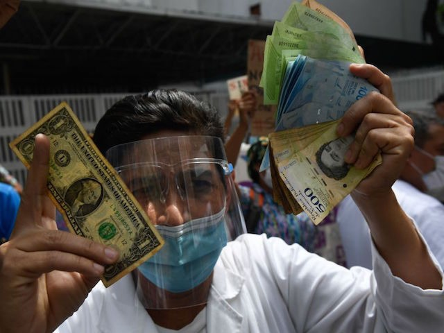 TOPSHOT - A health worker wearing a face mask and shield holds a one dollar bill in one hand and its equivalent in Bolivar bills -his salary- in the other, during a protest for the lack of medicines, medical supplies and poor conditions in hospitals, in Caracas on October 29, …