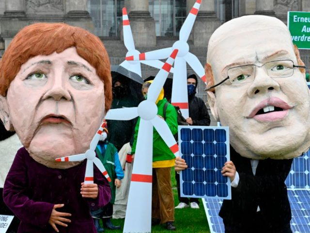 Climate and environmental activists dressed as German Chancellor Angela Merkel and German Economy Minister Peter Altmaier display mockups of tiny windturbines and solarpanels during a demonstration in front of the Reichstag, the building which houses the Bundestag (lower house of parliament), asking for more renewable energy, in Berlin on October …