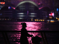 A woman pushes a baby stroller as she walks on a promenade that runs along Victoria Harbour in Hong Kong on December 14, 2020. (Photo by ANTHONY WALLACE / AFP) (Photo by ANTHONY WALLACE/AFP via Getty Images)