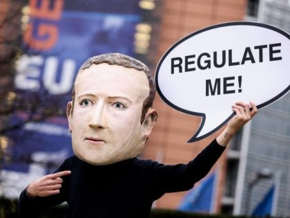 "An activist of environmental NGO Avaaz wearing a mask depicting Facebook CEO Mark Zuckerberg holds a banner reading ""Regulate me"" during an action marking the release of the Digital Services Act, outside the European Commission building in Brussels on December 15, 2020. - The European Union on December 15, 2020 …"