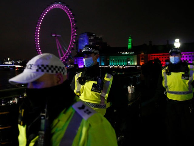 LONDON, ENGLAND - DECEMBER 31: Met Police officers attempt to disperse crowds gathered on Westminster Bridge on December 31, 2020 in London, United Kingdom. New Year's Eve Celebrations have been curtailed in the UK this year dues to Coronavirus pandemic restrictions. With most of the UK in tiers three and …