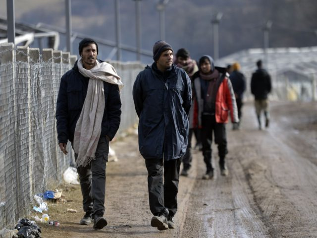 Illegal men walk along fence, at the Lipa camp near the north-western Bosnian town of Bihac, on January 7, 2021. - On January 5, the European Union's foreign policy chief called on Bosnia to assume responsibility for hundreds of migrants left sleeping out in the cold after their camp burned …