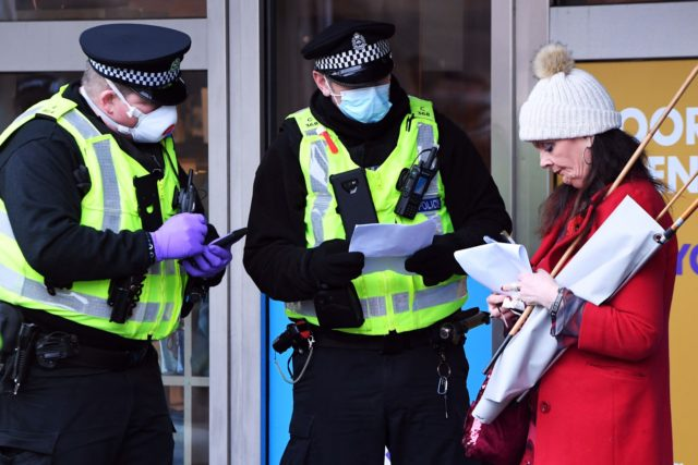 Police officers wearing PPE face masks speak to a protester outside the Scottish Parliament as members of the public attend an anti lockdown protest held by The Scotland Against Lockdown group in Edinburgh, Scotland on January 11, 2021. (Photo by Andy Buchanan / AFP) (Photo by ANDY BUCHANAN/AFP via Getty …