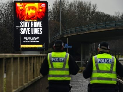 Police officers walk past a Covid-19 information board alongside the Clydeside Expressway in Glasgow on January 20, 2021. (Photo by Andy Buchanan / AFP) (Photo by ANDY BUCHANAN/AFP via Getty Images)