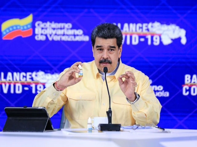 Handout picture released by the Venezuelan Presidency showing Venezuela's President Nicolas Maduro (C) speaking while showing a vial of Carvativir, during a televised message at Miraflores Presidential Palace in Caracas on January 24, 2021. - Carvativir is the latest in a series of remedies, without published medical studies allowing independent …