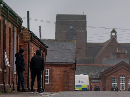 FOLKESTONE, ENGLAND - JANUARY 30: Asylum Seekers walk at Napier Barracks following a fire in one of the blocks that police have said was started deliberately, on January 30, 2021 in Folkestone, England. Napier Barracks, part of the disused Somerset House Sir John Moore Army Barracks, has been used since …