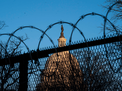 The exterior of the U.S. Capitol building is seen through barbed wire fencing at sunrise on February 8, 2021 in Washington, DC. The Senate is scheduled to begin the second impeachment trial of former U.S. President Donald J. Trump on February 9. (Photo by Sarah Silbiger/Getty Images)